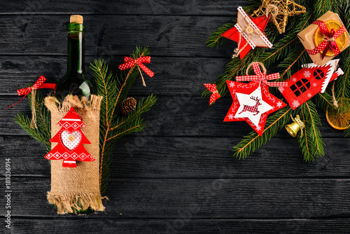 Christmas table serving, and a bottle of wine. New Year. Christmas tree and Christmas tree decorations. On a wooden background. Free space for text. - 181036914