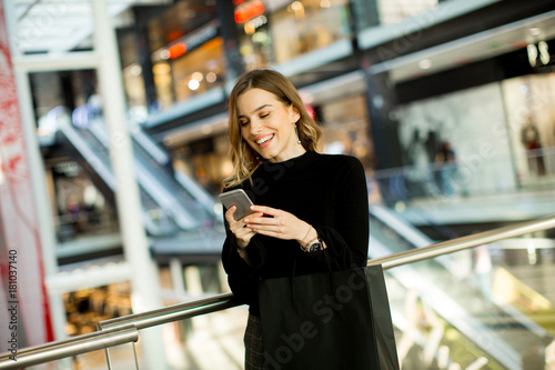 Lovely young woman looking on mobile phone in shopping center Poster