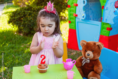 Baby toddler girl in outdoor second birthday party clapping hands at cake with Teddy Bear as best friend, playhouse and tea set Poster