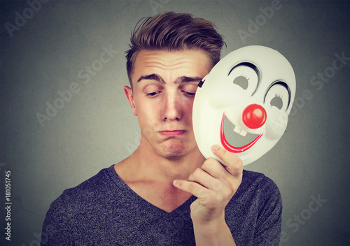 Young sad man taking off happy clown mask isolated on gray background. Human emotions.