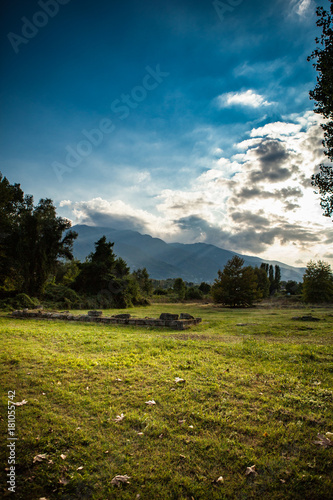 Foto op Aluminium Herfst Nature Autumn scene with green fields, trees and mountain, under the blue sky and sun