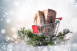 Christmas gift boxes in kraft paper in a shopping cart or trolley on fir branches, snowy bokeh light background, copy space - 181066957