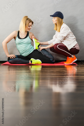 Poster Woman in sportswear stretching legs with trainer