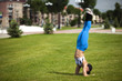 girl practicing yoga in the city on green grass