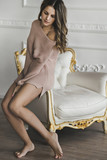 Sensual tenderness woman in light pink sweater at white antic interior