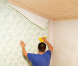 Man glues the wallpaper to the wall in the house - 181101996