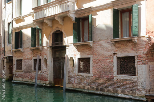 Fototapeta walk through the charming, narrow streets of Venice, typical but magical view - canals, bridges and old tenements with green shutters