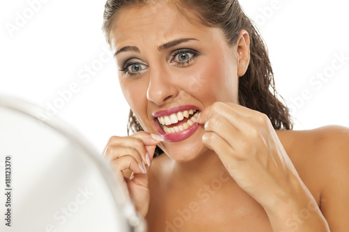 young nervous woman cleans her teeth with dental floss