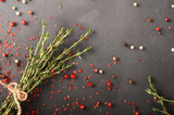 Thyme bundle decorated with pepper on black background top view with place for text - 181126199