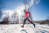 Man running on the snow in a forest