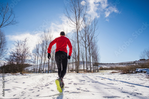 Tuinposter Jogging Man running on the snow in a forest