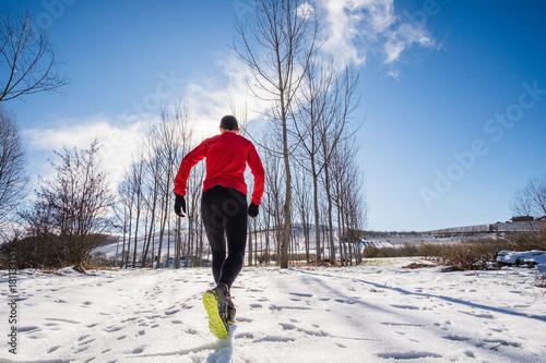 Fotobehang Hardlopen Man running on the snow in a forest