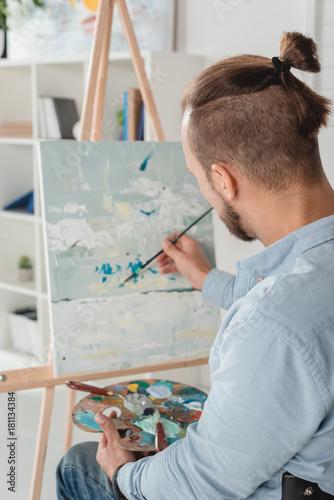 Fototapeta man painting on canvas