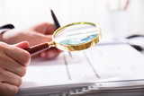 Businessperson Checking Bill With Magnifying Glass - 181134720