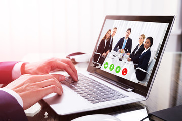 Close-up Of A Businessperson's Hand Video Conferencing On Laptop