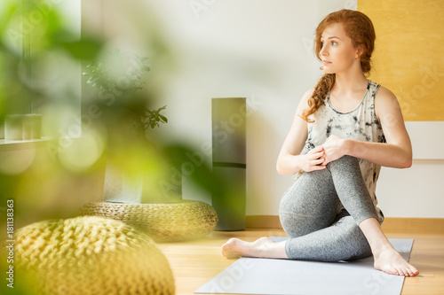 Poster Young sportswoman stretching on mat
