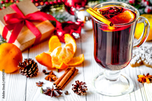 Fototapeta Christmas mulled wine with spices in cup on wooden background