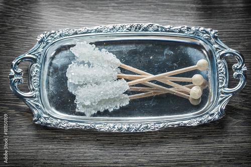 Sugar sticks metallic tray on wooden board