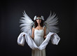 Woman in white dress with angel wings.