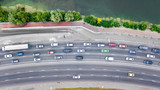 Aerial top view of road by river from above, automobile traffic and jam of many cars, city transportation concept