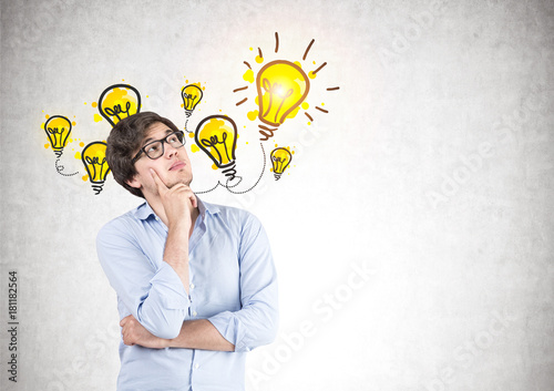 Pensive young man in glasses, light bulb
