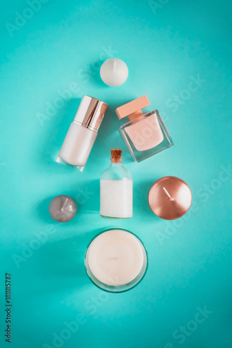 Spa beauty products flatlay in shape of Christmas tree on turquoise colored background. Coconut oil, luxury cream, serum, perfume, candles.