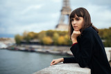 Beautiful young Parisian woman in long coat near the Eiffel tower on a autumn day - 181189730