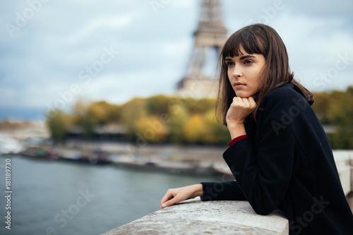Fototapeta Beautiful young Parisian woman in long coat near the Eiffel tower on a autumn day