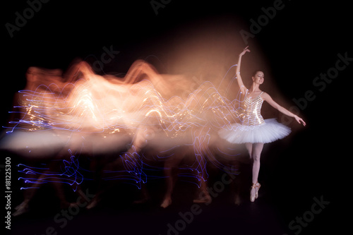 Young female / woman / girl ballerina in a white pack / tutu solo dancing doing stand on toes and leaves light leak trail of silhouette in black scene with reflecting floor and dark background