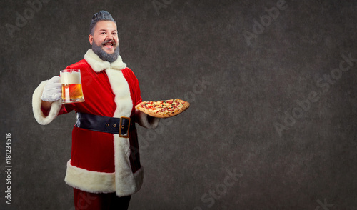 Fototapeta Santa with pizza and a glass of beer in his hands at Christmas on a background of copyspase.