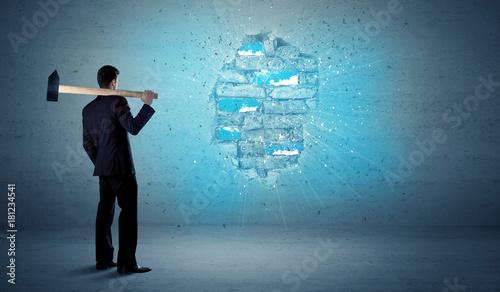 Fototapeta Business man hitting brick wall with huge hammer