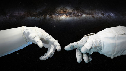 two near touching hands in space suits, Michelangelo touch pose with Milky Way galaxy