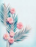 Creative layout with tropical palm leaves and pastel pink flowers on  turquoise blue desktop background, top view, place for text, vertical - 181236930