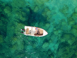 Aerial survey of a couple on a boat sunbathe together on a warm summer day
