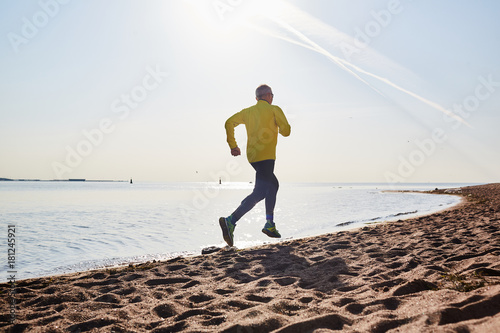 Wall mural Active pensioner running along coastline on sandy beach in the morning