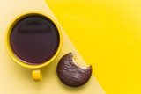 yellow mug with black coffee and a chocolate macaron on a yellow background.