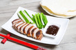 Baked duck with hoisin sauce, pancakes, cucumbers and shallots. Selective focus, close-up.
