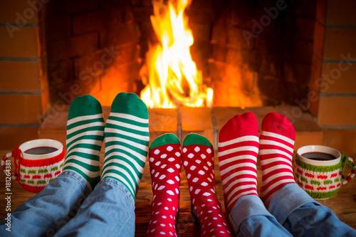 Family in Christmas socks near fireplace