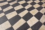 Outdoor street tiles with geometric pattern.The texture of perspective colored checkered tile in the street.