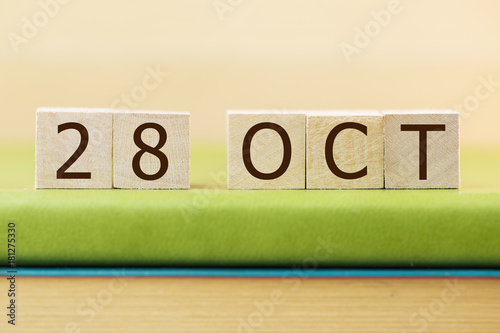 Poster Wooden cube shape calendar for OCT 29 on green book, table.