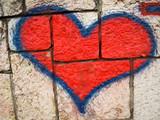 red heart graffiti on brick wall as declaration of love