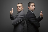 Two Businessman Posing On The Gray Wall - 181289514