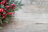 Fototapety Christmas Evergreen Branches and Berries in Corner Over Rustic Wooden Background