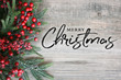 Merry Christmas Text with Christmas Evergreen Branches and Berries in Corner Over Rustic Wooden Background - 181293712