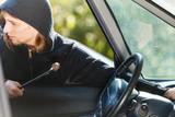 Thief burglar breaking into car - 181307104