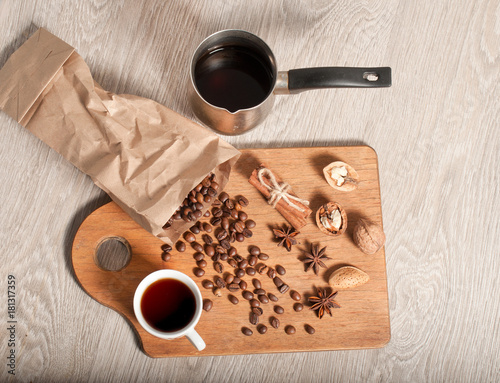 Papiers peints Café en grains A cup of black coffee and coffee beans on a wooden table. The concept of the morning. banner for a cafe, top view