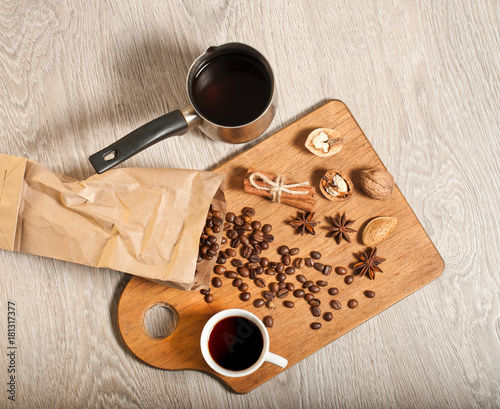 A cup of black coffee and coffee beans on a wooden table. The concept of the morning. banner for a cafe, top view