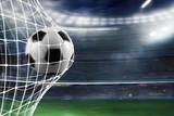 Soccer ball scores a goal on the net - 181319793