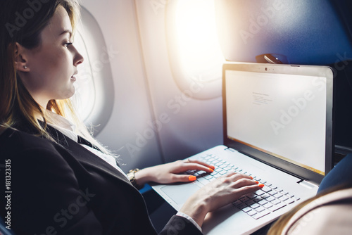 Young female student learning online via netbook while sitting in an airplane cabin