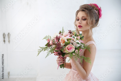 Portrait of an elegant bride with a bouquet of roses in her hands.